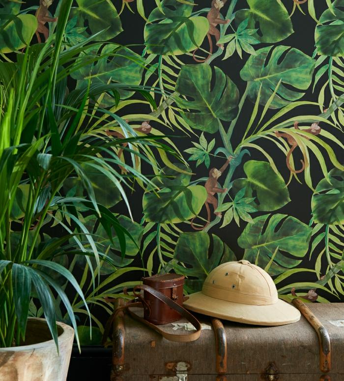 papier peint liberty aux motifs jungle, grandes feuilles vertes, chapeau à la Indiana Jones, avec appareil photographique vintage, grande malle vintage, grand pot blanc avec palmier