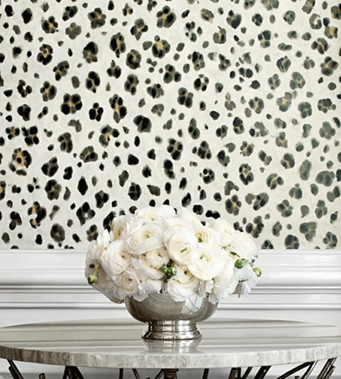 papier peint trompe l'oeil aux motifs taches de léopard, papier peint en blanc, noir et vert, table ronde avec plan en marbre, vase de fleur bas couleur argent avec des roses blanches