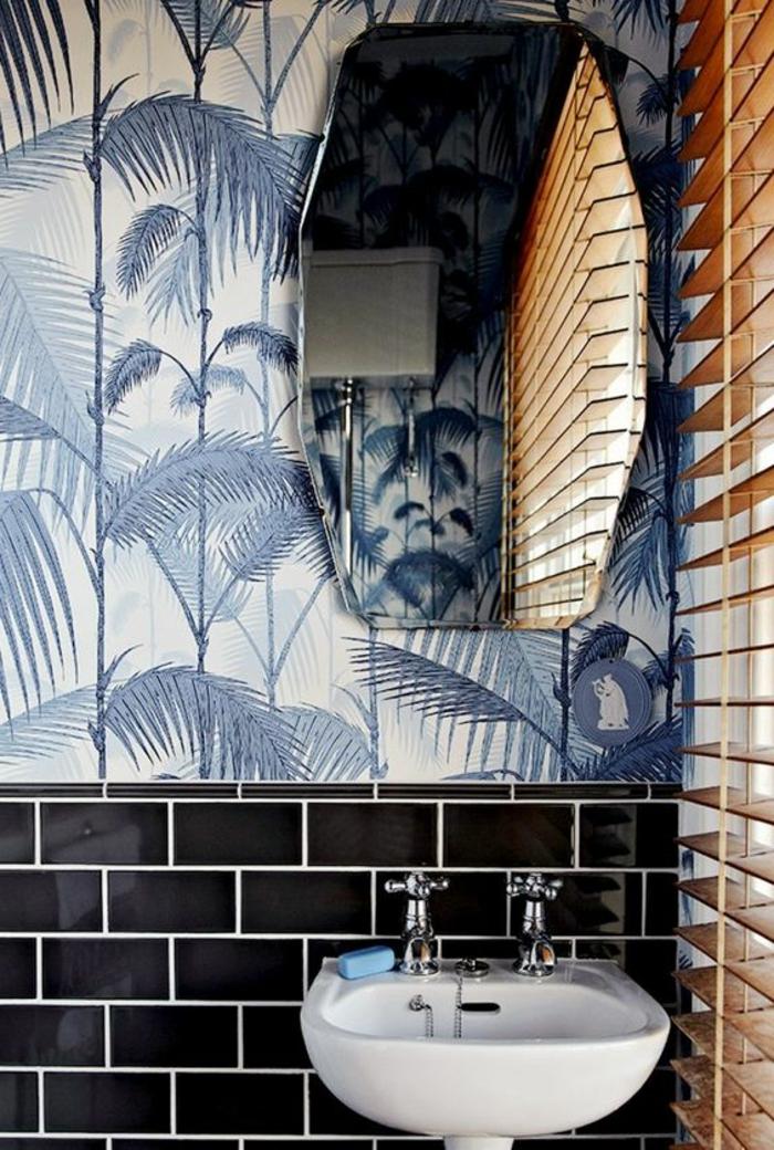 papier peint liberty avec des grandes feuilles de palmier en couleur bleue, miroir en forme géométrique, moitié du mur en briques noires, petit lavabo blanc à deux robinets, stores en beige