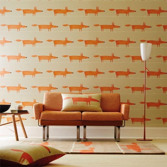 poster geant papier peint trompe l'oeil avec des renards oranges sur fond beige, lampadaire sur pied en couleur brique avec abat-jour blanc, tapis carré beige avec des renards oranges, grand coussin avec des renards oranges
