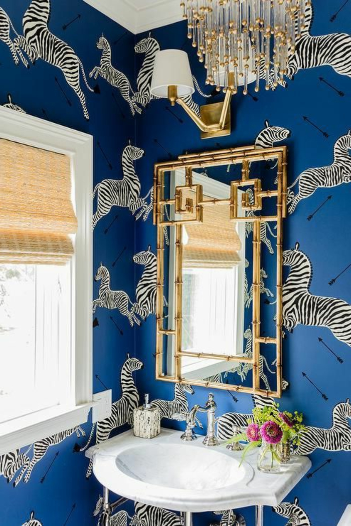 papier peint trompe l'oeil en bleu électrique avec des grands motifs zèbres qui courent, salle de bains avec grand lustre aux pampilles longues en cristal, lavabo blanc, en forme ovale et carrée