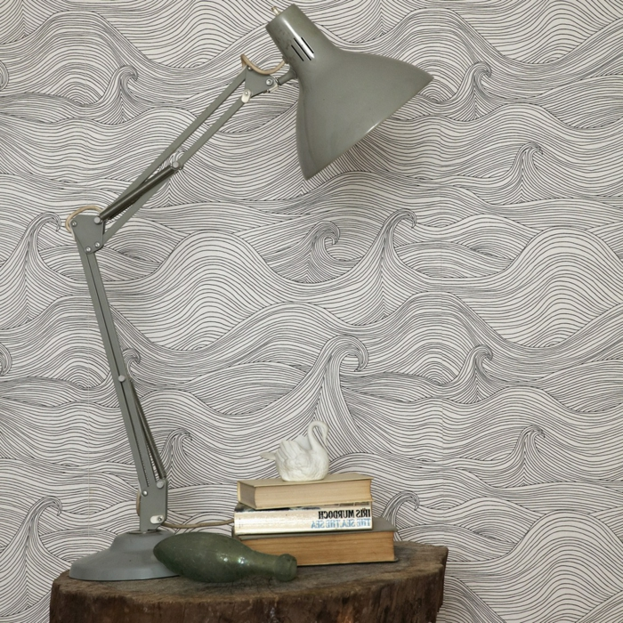 papier peint trompe l'oeil aux motifs ondes grises, mer agitée, meuble de chevet en forme de tronc d'arbre, lampadaire de chevet en métal gris, 3 livres format de poche sur le meuble de chevet, cygne blanc petite taille comme objet décoratif