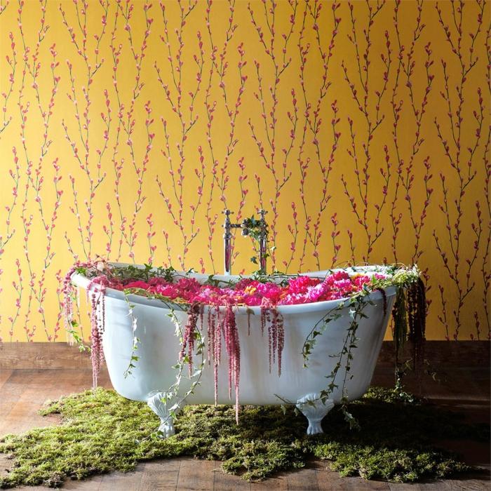 papier peint liberty en jaune moutarde et petites fleurs délicates en rose, salle de bains avec baignoire ovale blanche style vintage, sol recouvert de parquet marron foncé en PVC, décoration herbes et fleurs artificielles en vert et rose autour de la baignoire