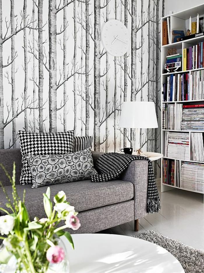 papier peint intissé aux motifs arbres dans une forêt, en couleurs gris et noir, canapé gris avec des grands coussins aux motifs carrés et géométriques, lampadaire sur pied bas avec abat-jour tambour, posé sur table blanche ronde, tapis gris