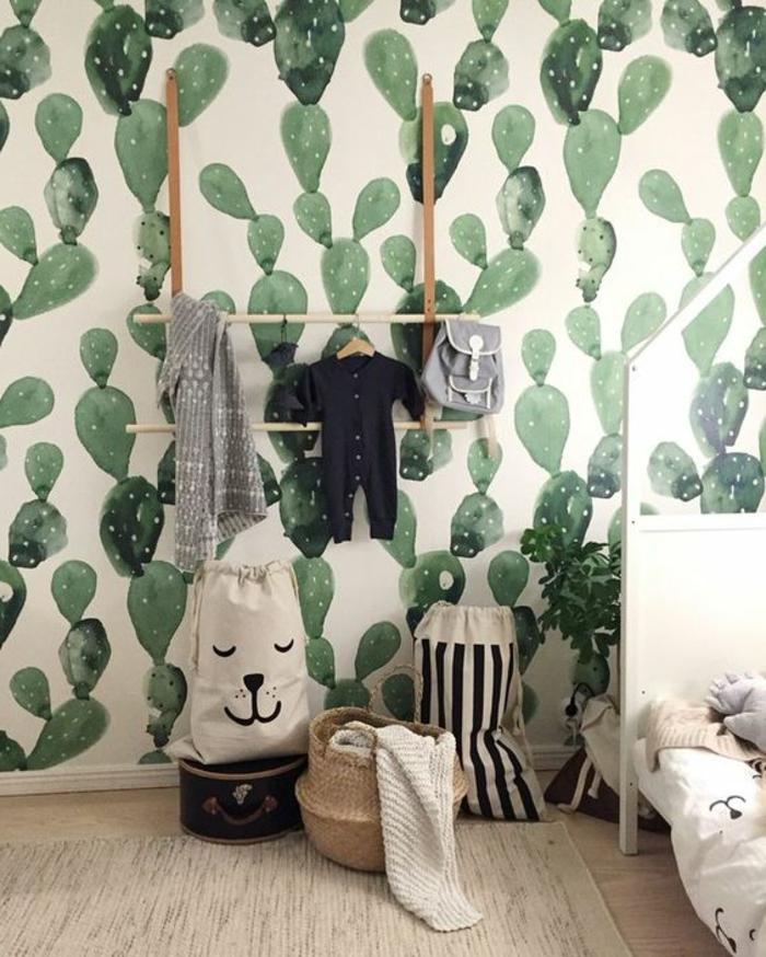 poster geant avec des motifs grands cactus verts sur fond blanc, lit en blanc, étagères en beige et marron, sacs de rangement à rayures et avec un visage de chat, parquet beige et tapis en beige, avec des taches marron