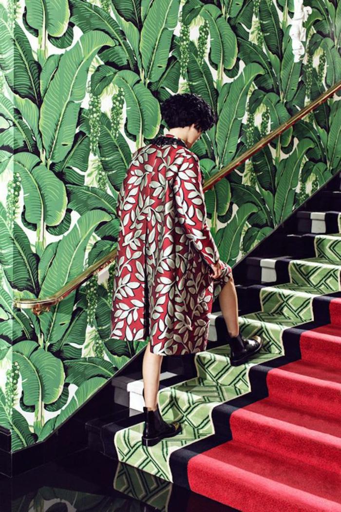 poster geant aux motifs grandes feuilles vertes sur fond blanc, escalier avec tapis roulant en rouge, noir et vert, bords escalier en granit noir brillant