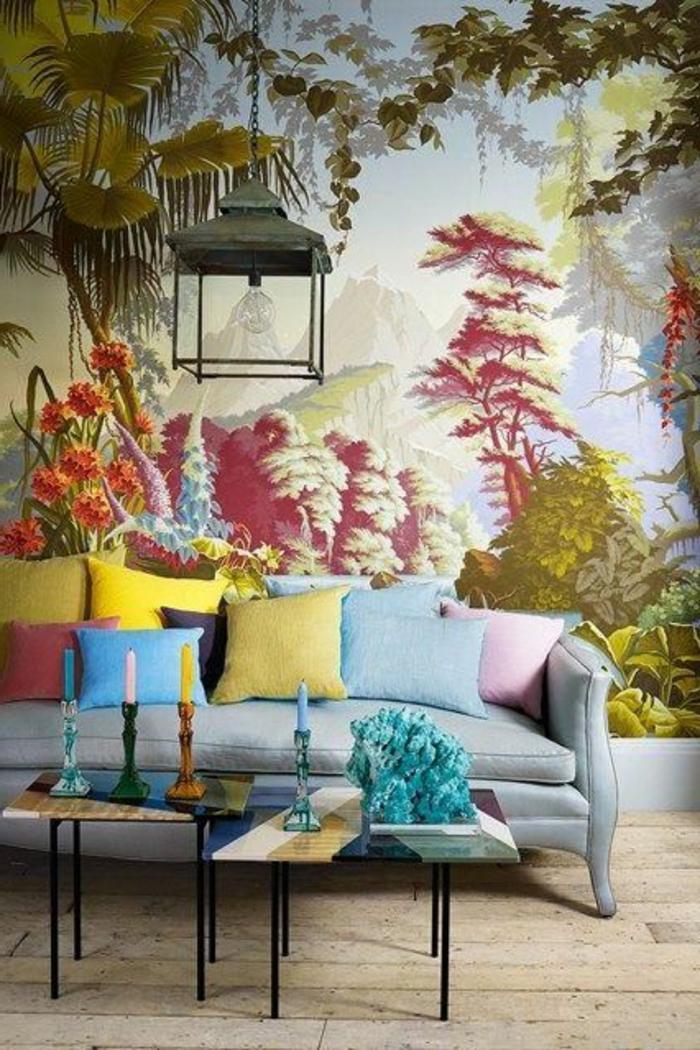 papier peint liberty en couleurs vives motifs forêt Amazonienne, meubles en style asiatique, deux tables basses avec des pieds en métal noir, parquet en beige clair, canapé en bleu pastel, des bougeoirs en 3 couleurs bleu, vert et jaune