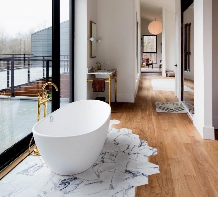 plancher salle de bain, revêtement de sol avec parquet de bois et carrelage à design marbre, modèle de baignoire blanche avec robinet doré