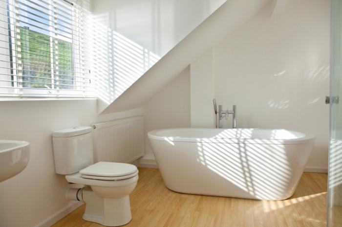 amenagement salle de bain, déco aux murs blancs et plancher en bois avec baignoire et cuvette wc blancs