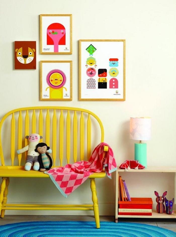 customiser un meuble de peinture jaune, un banc repeint dans la chambre enfant, tapis bleu, deco murale de cadres, jouets