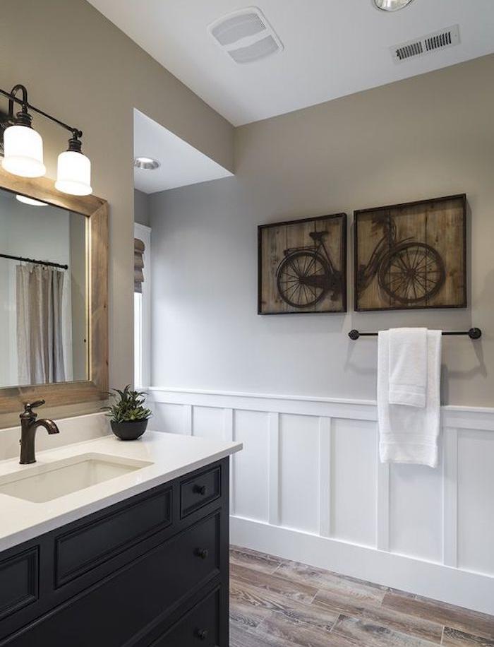 peinture couleur ficelle clair, nuance taupe clair dans une salle de bain avec meuble salle de bain marron, miroir rectangulaire, parquet marron, deco murale de panneaux en bois dessin bicyclette