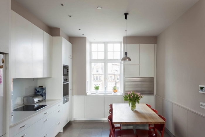 amenagement cuisine salle à manger couleur taupe clair, meuble cuisine blanc, table en bois entourée de chaises rouges