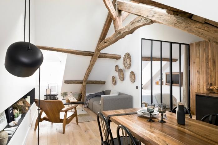 comble aménagé, transformation du grenier en pièce avec canapé gris et coin à manger en table de bois et chaises noires