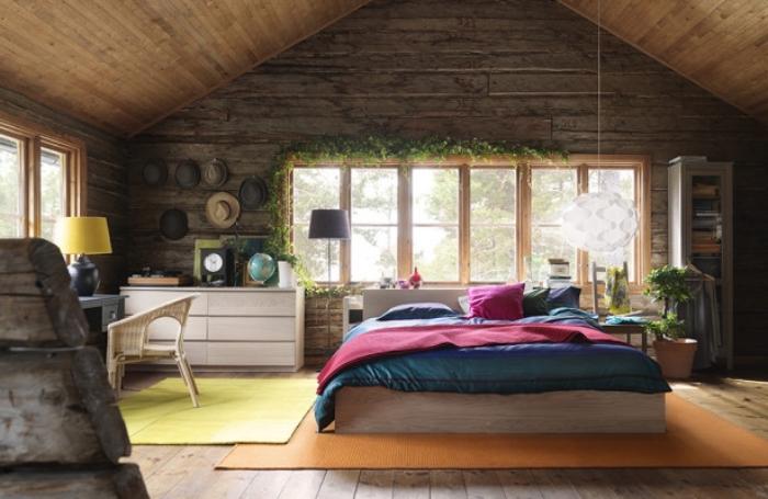 chambre mansardée, cadre de lit en bois avec couverture de lit vert et rouge, bureau en bois peint gris et chaise beige