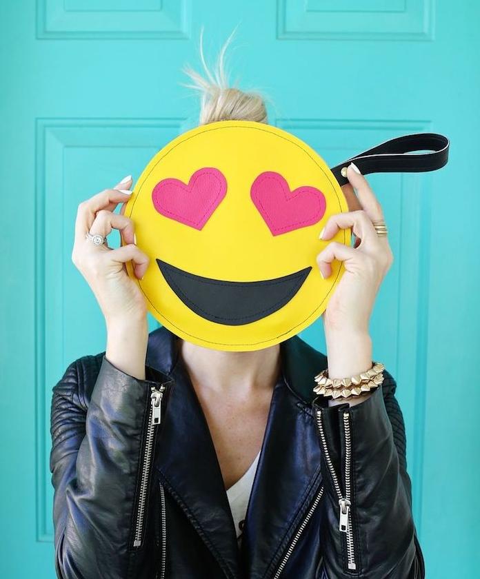 idée cadeau noel ado fille, pochette emoji jaune pour y mettere son smartphone, porte monnaie et affaires personnels, fille avec veste en cuir