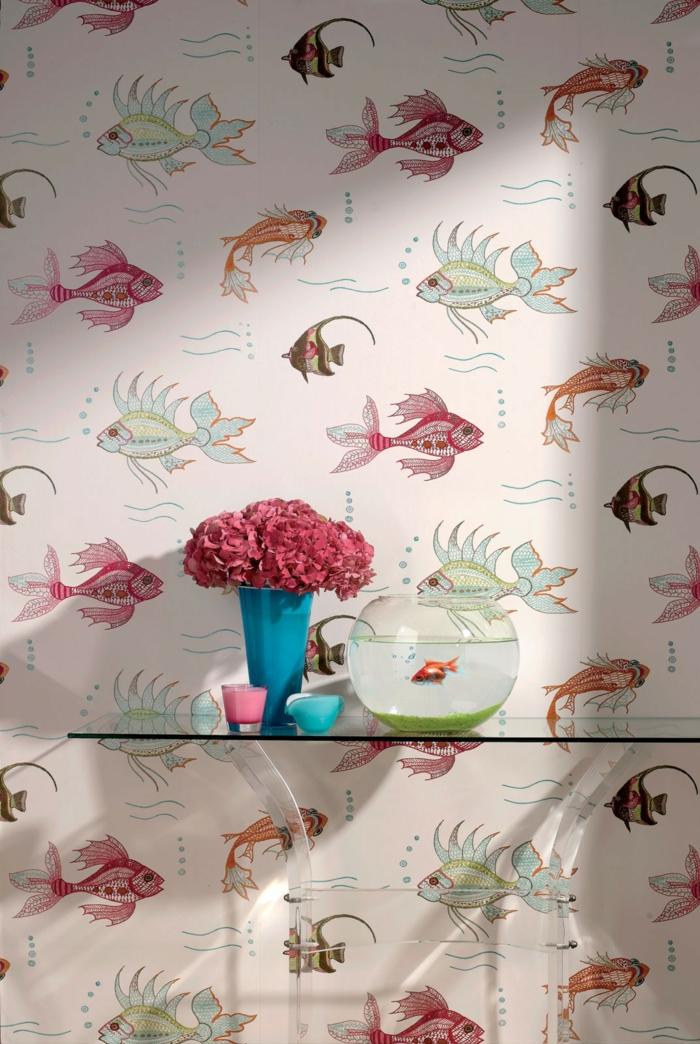 papier peint trompe l'oeil aux motifs poissons en couleurs vives qui nagent, mur d'entrée, table en verre blanc rectangulaire, bol avec poisson rouge, vase en turquoise avec des fleurs roses, deux bougies aromatisées en rose et bleu turquoise