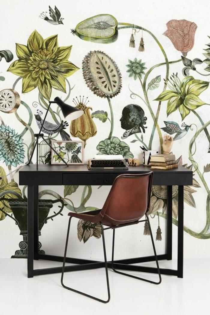 papier peint trompe l'oeil avec des grandes plantes et herbes, en vert, rouge, gris foncé, mur d'un bureau à la maison, table noire en bois avec des pieds en métal noir, chaise en métal noir, partie du dossier en couleur whisky, sol en blanc