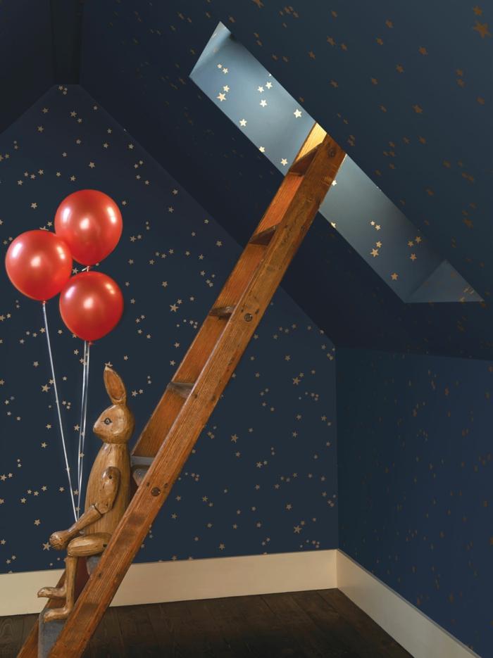 papier peint trompe l'oeil aux motifs ciel étoilé pour une chambre d'enfant sous les combles, avec fenêtre, parquet en marron foncé, escalier en bois clair, lapin en bois avec trois ballons rouges