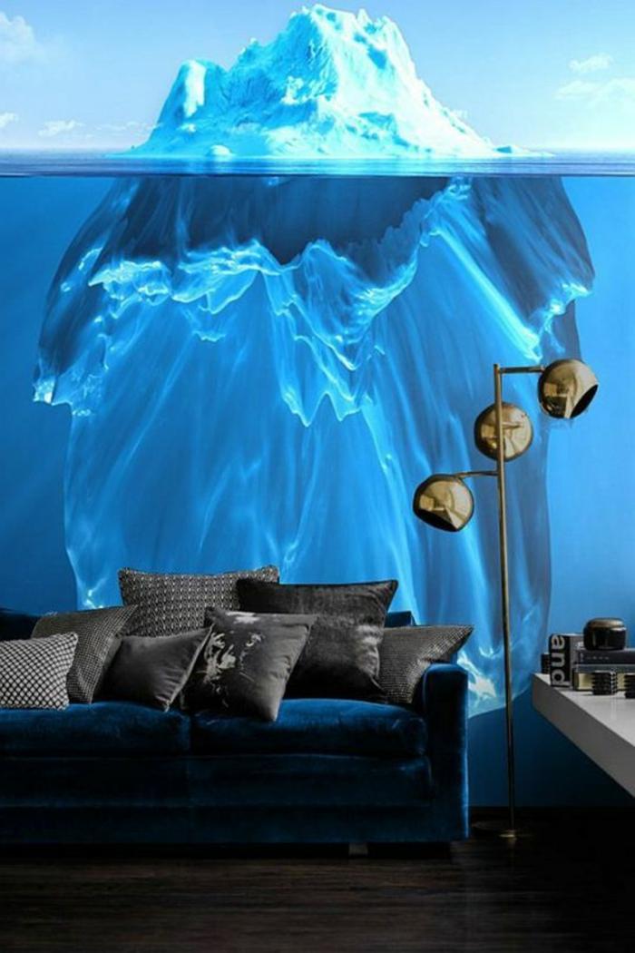 papier peint trompe l'oeil au motif grand iceberg, qui montre un bout, eau bleue transparente avec la base de l'iceberg, canapé en velours bleu, parquet brut en couleur marron foncé, luminaire sur pied haut avec trois boules en métal couleur bronze