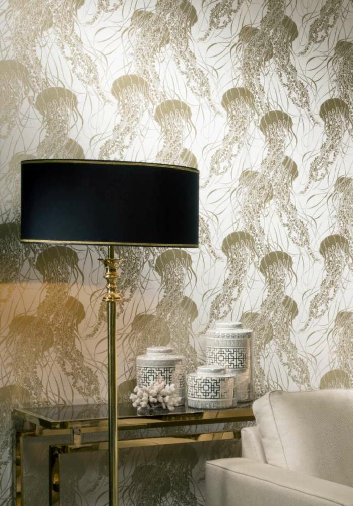 papier peint intissé aux motifs méduses en couleur bronze, coin de salon avec table en verre trempé et pieds en métal couleur or, fauteuil blanc en faux cuir