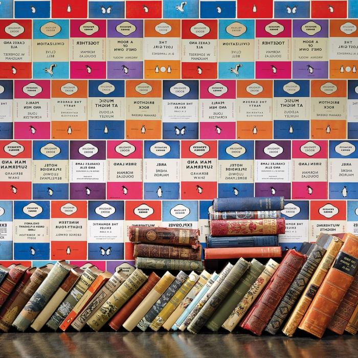 papier peint trompe l'oeil avec des motifs BD en bleu, fuchsia et rouge, murs d'une bibliothèque avec beaucoup de livres, titres anciens, couvertures usées