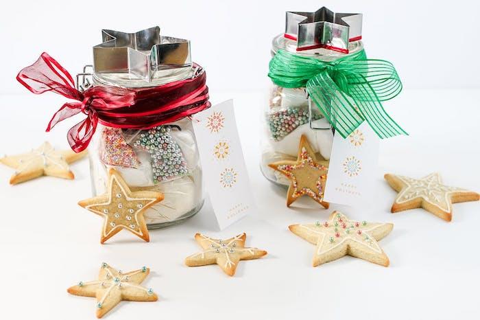 cadeaux de noel pour femme, pot en verre décoré de ruban et remplis de produits et ingrédients pour faire des sablés de noel
