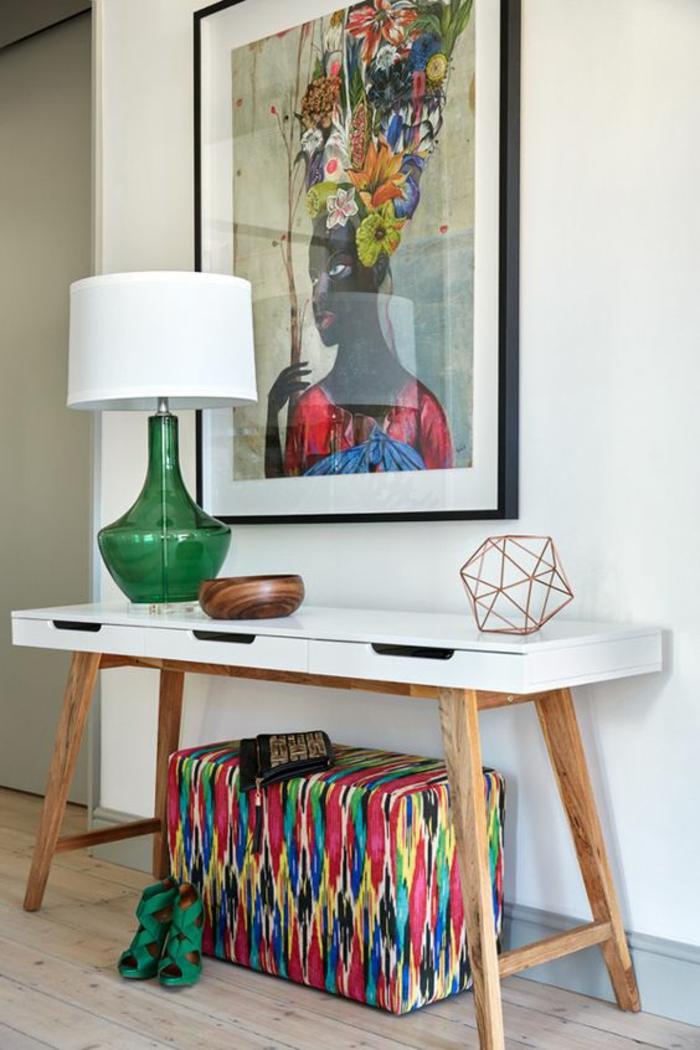 comment decorer un couloir en style ethnique africain, table avec des pieds en bois clair et plan blanc, lampadaire avec base en vert bouteille et abat-jour blanc, malle de rangement en couleurs vives, tableau avec femme africaine en tonalités chaudes, parquet en bois clair