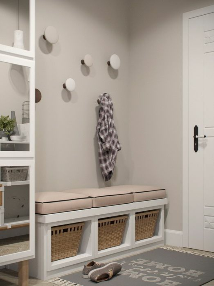 comment decorer un couloir en gris et taupe, grandes patères rondes en blanc, banc en blanc avec des niches au-dessous avec des paniers pour rangement, trois coussins en rose sur le banc blanc, porte blanche, tapis gris avec inscription, baskets grises sur le tapis