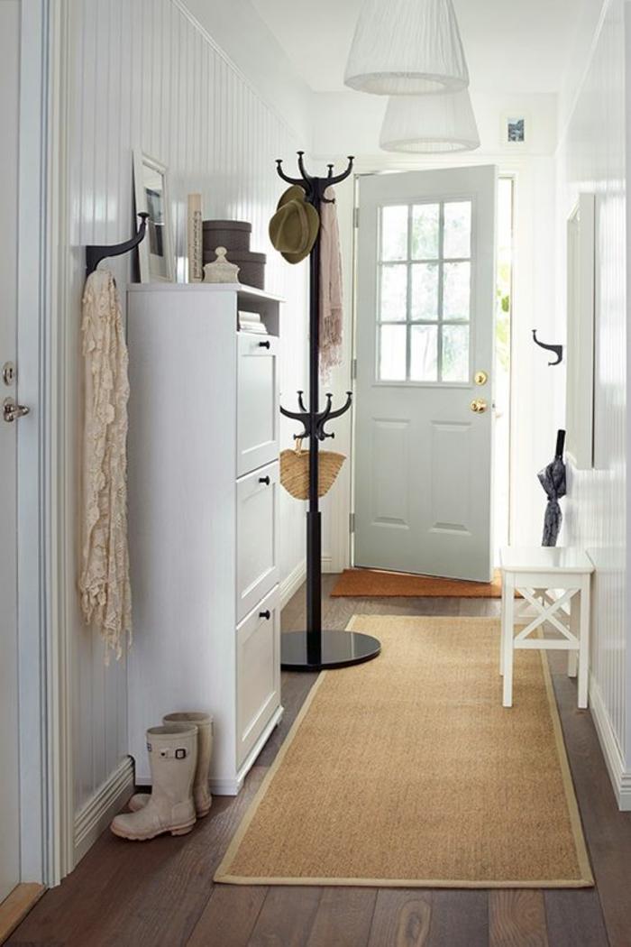 comment decorer un couloir, tapis beige, deux luminaires blancs suspendus en forme de cônes, porte-manteau classique en métal noir, banc blanc, patère en métal noir, porte en couleur pistache
