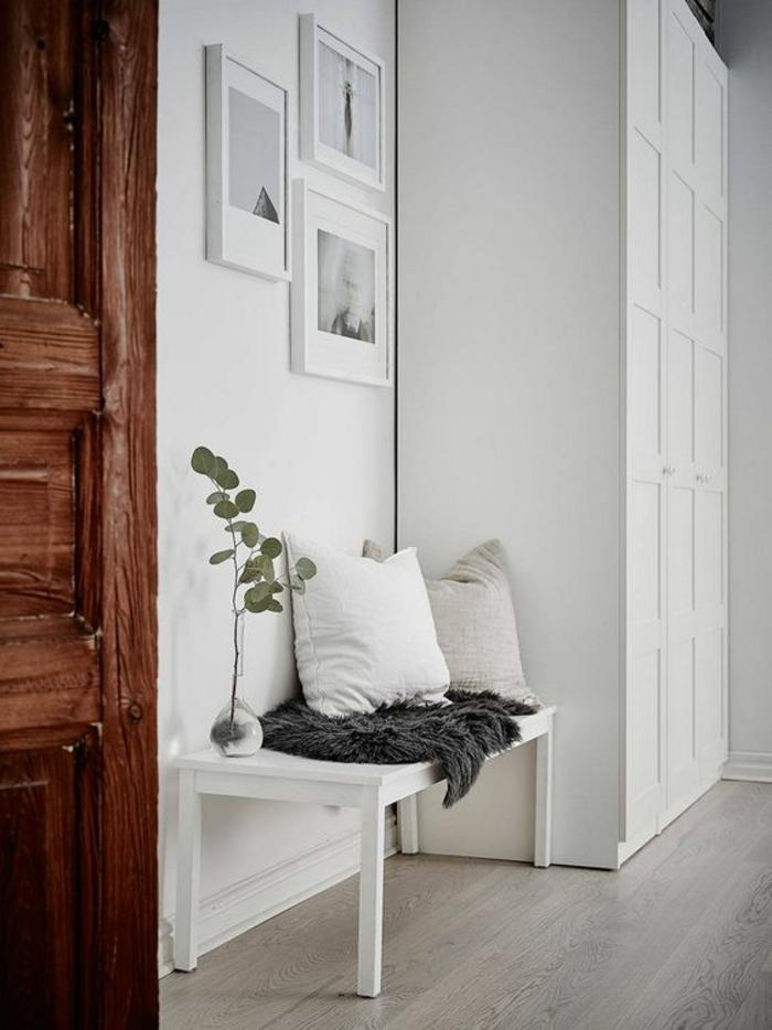 comment decorer un couloir en blanc et gris, trois tableaux en cadre blanc sur le mur blanc, grande armoire blanche avec des motifs décoratifs carreaux, porte en bois marron foncé