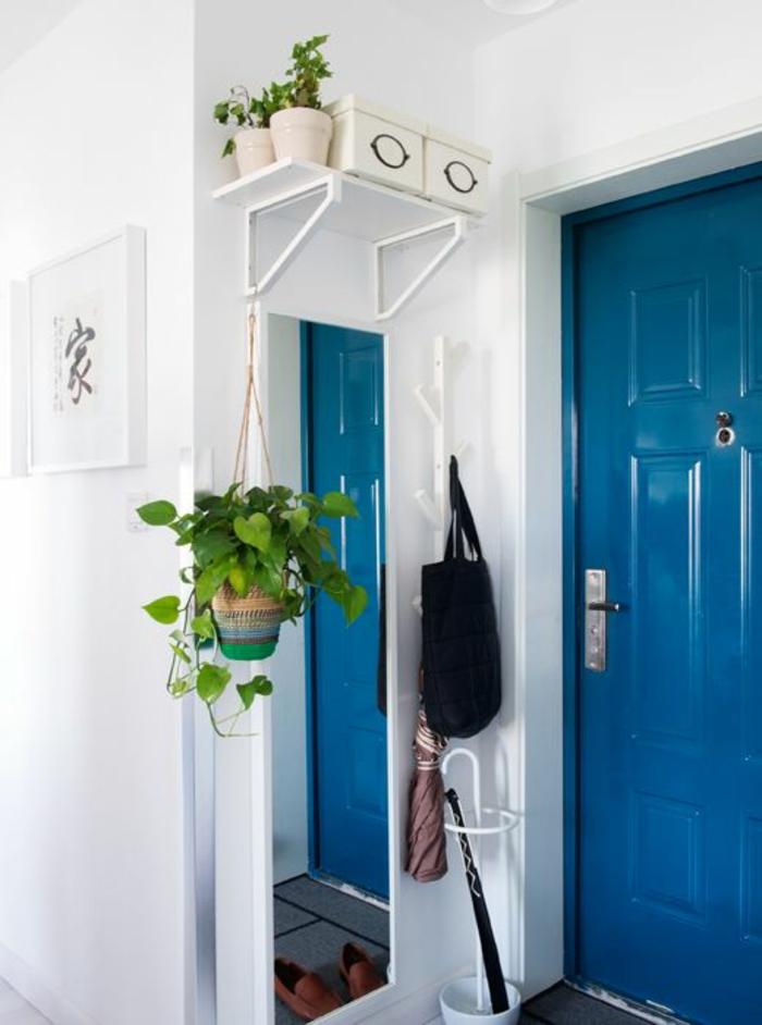 comment decorer un couloir en blanc et en bleu électrique avec étagère blanche au-dessus d'un grand miroir rectangulaire, porte-parapluie en métal blanc