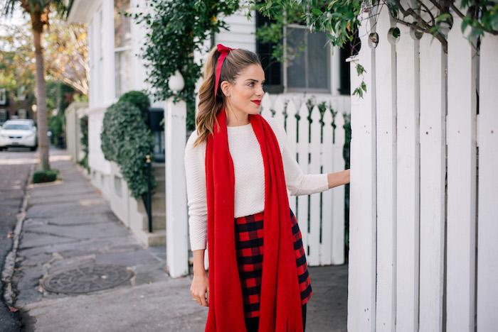 exemple de coiffure de noel simple, queue de cheval bouclée et accessoirisée de ruban rouge, tenue pour noel blanc, rouge et noir