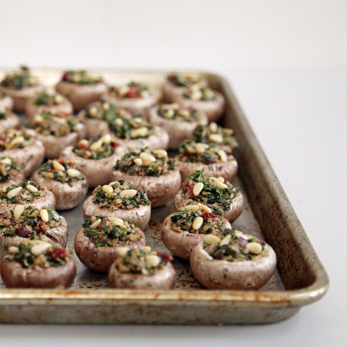 repas dinatoire végétarien de champignons farcis aux épinards, tomates séchées, pignons et roquette