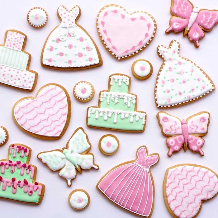idée comment réaliser une recette glace royale sur des biscuits en formes diverses couverts de glaçage rose, blanc et vert, motif robe, gâteau, papillon et coeur