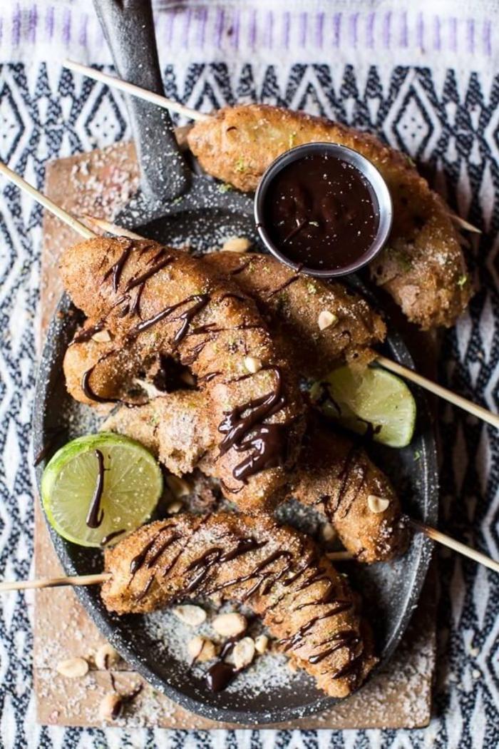 une idée apéro rapide et originale pour un repas entre amis, recette de brochettes de beignets à la banane et à la sauce au chocolat épicée à la mexicaine