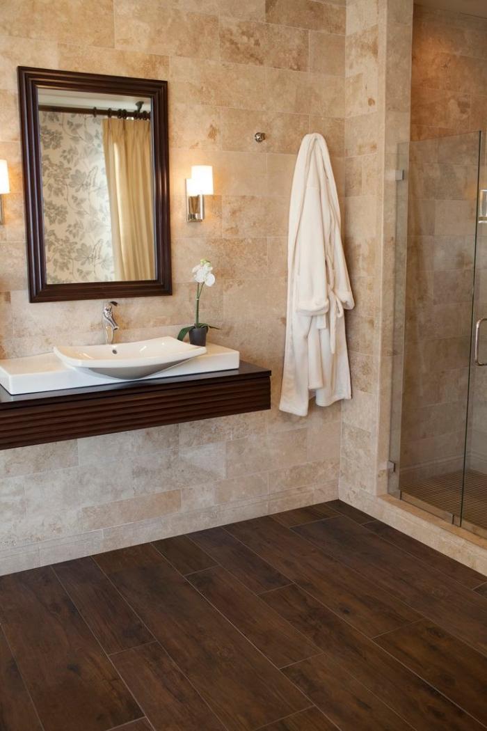 revetement salle de bain, cabine de douche en verre et carrelage beige avec plancher en bois foncé