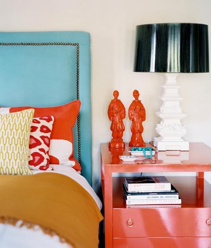 renover table en bois, customiser un meuble, table de nuit de peinture rouge, statuettes rouges, lampe noire avec pied blanc, tete de lit bleue, linge de lit jaune, blanc et rouge