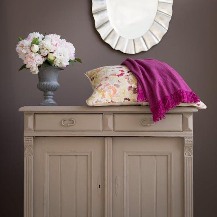 meuble relooké, commode repeinte de couleur grise, couverture mauve et coussin coloré à imprimé floral, bouquet de fleurs, mur gris foncé, miroir rond