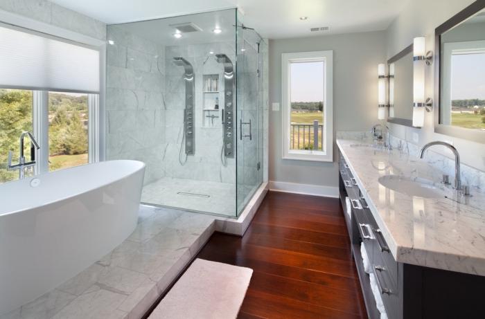plancher salle de bain, carrelage à design blanc marbre et cabine de douche en verre, meubles de bain en bois noir et finitions métalliques