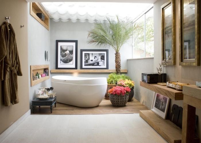 recouvrir carrelage sol, déco salle de bain avec plantes exotiques et meubles en bois clair, cadre de photo noir avec photos blanc et noir