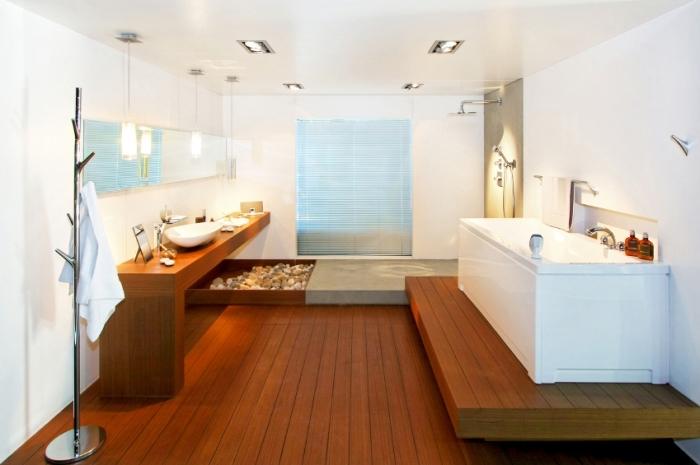amenagement salle de bain, ambiance zen avec galets, meubles et plancher en bois foncé avec murs et plafond blanc
