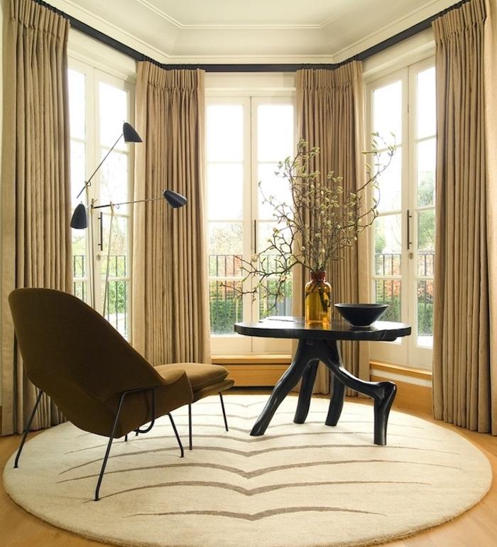 rideaux couleur taupe clair, chaise longue teinte marron foncé, tapis beige, table d appoint noire design, parquet clair, branches dans une bouteille en verre