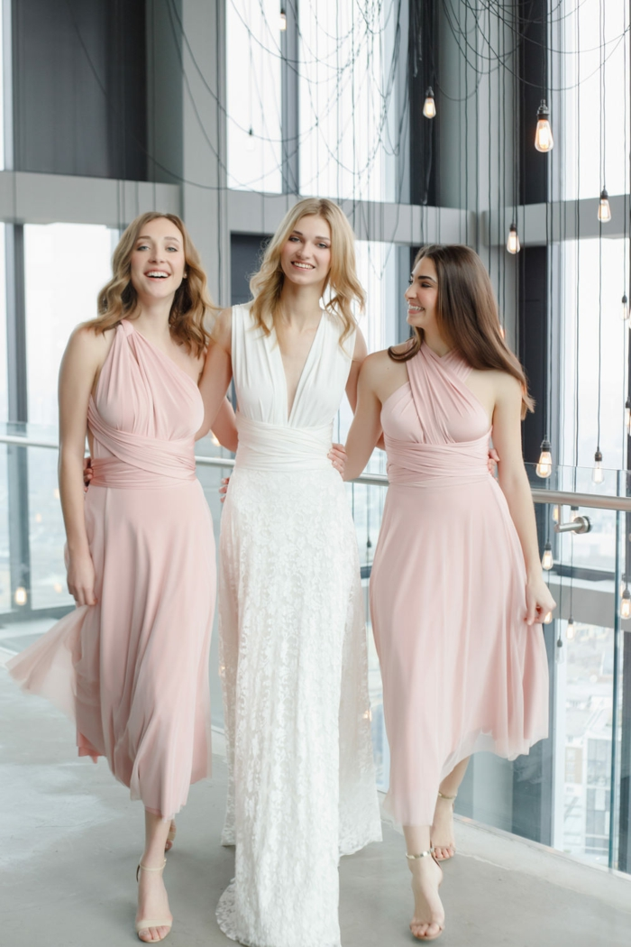 tenue de mariage femme pour les demoiselles d'honneur en rose, robe de la mariée en blanc coupe simple, avec décolleté en V, longueur maxi