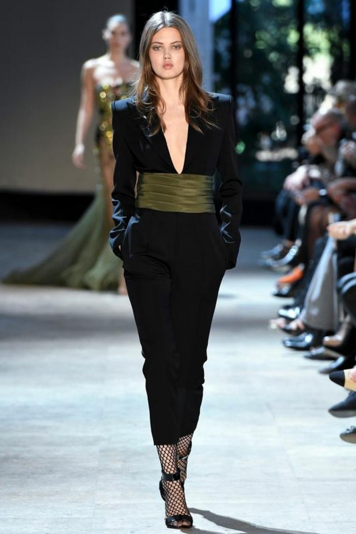 tenue pour mariage, combinaison en noir, avec large ceinture en tissu vert drapé, top avec décolleté échancré profond, pantalon moulant, manches longues, style très élégant