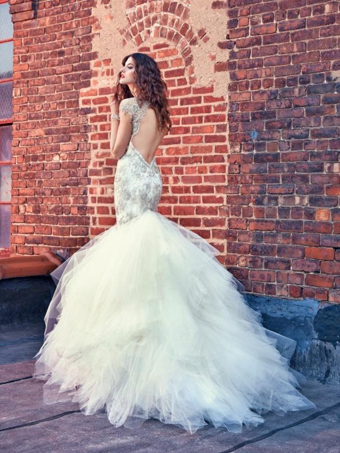 tenue pour mariage en dentelle blanche et en tulle blanc avec le dos nu, manches courtes avec des brocarts argentés, partie moulante et traîne en tulle blanc asymétrique