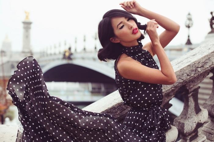 robe habillée pour mariage, coupe de cheveux mi-longs noir et bouclés, maquillage avec eye-liner et rouge à lèvres, robe noir et blanc