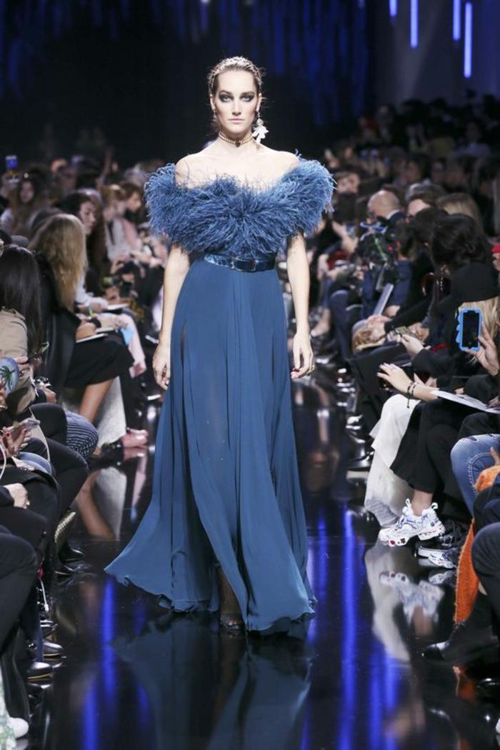 tenue de mariage femme, robe longue, en bleu royal avec des plumes autour du décolleté, ceinture fine avec finition brillante en bleu marine