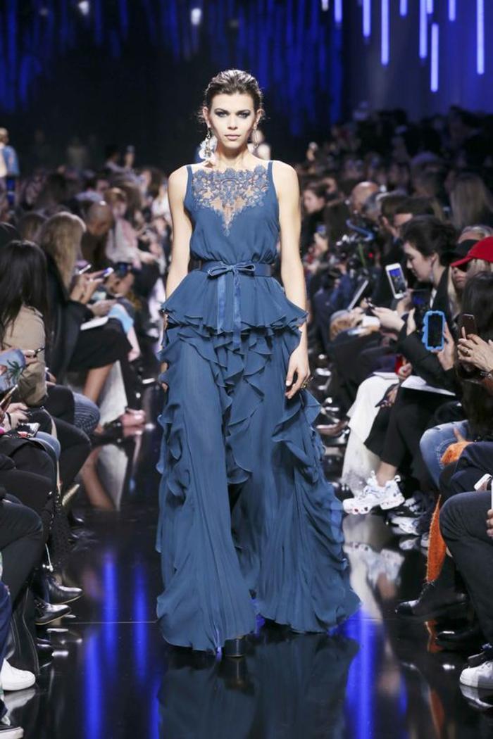 tenue de mariage femme en bleu indigo, volants tout au long de la jupe, zone du décolleté recouverte de dentelle bleue, ceinture en tissu, style vestimentaire Renaissance