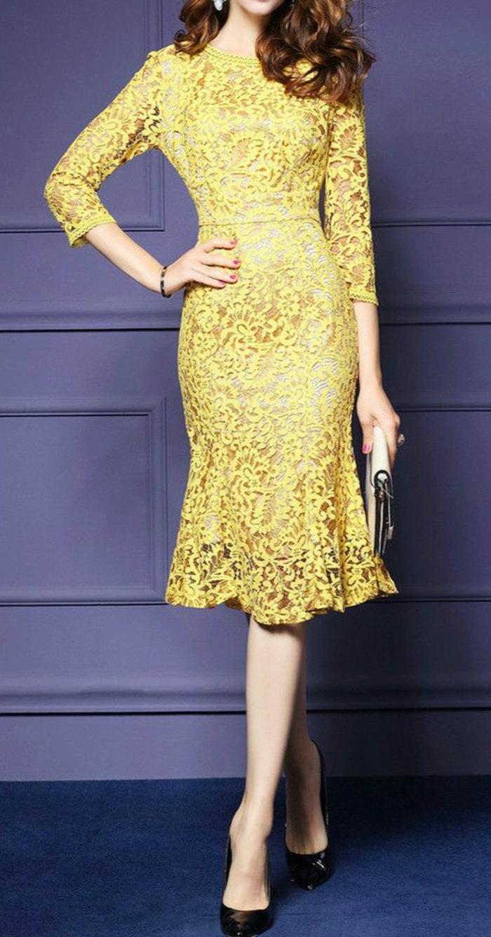 robe pour mariage en dentelle jaune, avec des manches 3/4, longueur jusqu'aux genoux, modèle semi-transparent, escarpins noirs pointus, avec grande pochette blanche