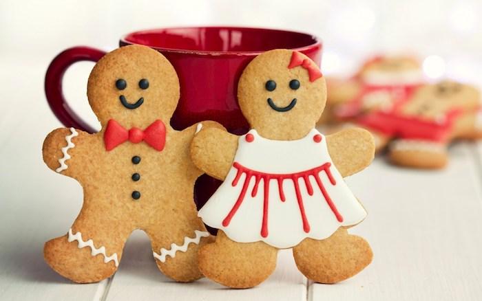 dessert de noel original, bonhommes en pain d'épices, fille et garçon mignons avec des vêtements et traits de visage au chocolat